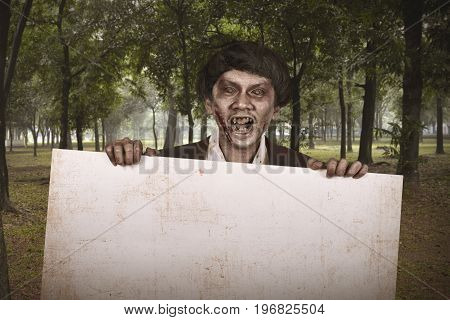 Spooky Asian Zombie Man In Suit With Empty Banner