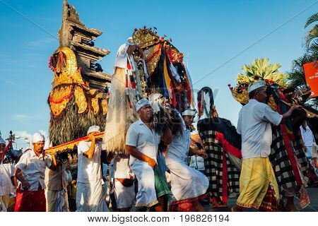 BALI INDONESIA - MARCH 07: Balinese people in traditional clothes carry jempana or wooden litter at the procession during Balinese New Year celebrations on March 07, 2016 in Bali, Indonesia.