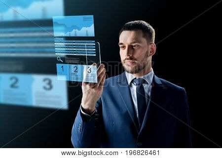 business, augmented reality and modern technology concept - businessman working with transparent smartphone and virtual exchange charts projections over black background