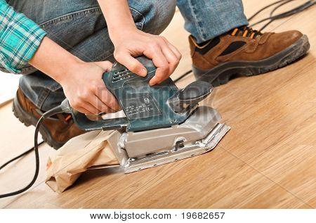 detail of carpenter at work with sander on wood floor