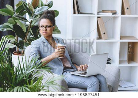 Portrait Of Pensive African American Businesswoman With Coffee To Go In Hand And Laptop On Knees Loo