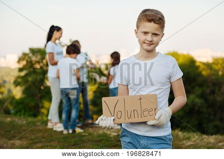 Social works. Positive teenager standing on the foreground and holding carton in both hands while posing on camera