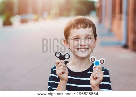 Little Child Boy Playing With Fidget Spinner Outdoors