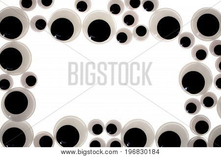 Googly eye border. A frame of funny toy eyes. Jiggly eye plastic craft item used in fun toy making.