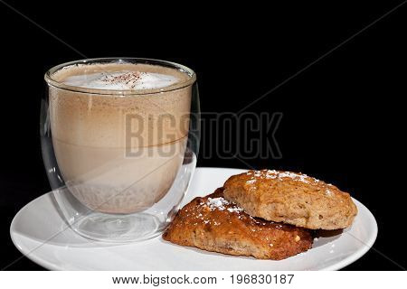 Coffee break. Cappucino coffee and home-made biscuits on a white plate against black background with copy space.
