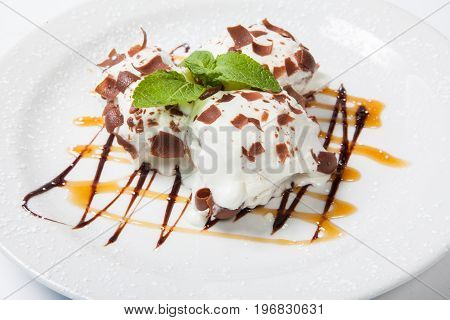 Ice Cream With Chocolate Topping.dessert Is On The White Plate