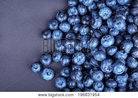 A view from above on a heap of nutritious blueberries on a bright purple background. Tasteful and ripe blueberries. Refreshing and healthful blueberries for sweet summer smoothies and yogurts.