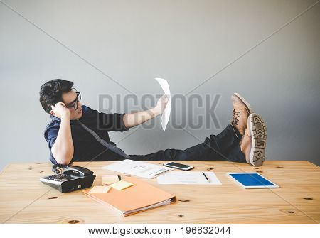 Businessman relaxing and working at desk in creative office