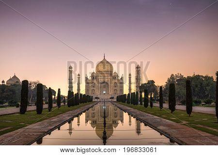Taj Mahal shot at night with moon light at Yamuna river at sunset Agra, India.