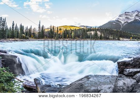 The full-water bubbling waterfall of Athabasca. Cold blue water at sunset. Clear autumn evening in Canada. The concept of extreme and ecological tourism
