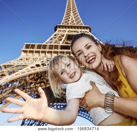 Happy Mother And Daughter Handwaving Against Eiffel Tower