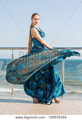 A charming girl in a long turquoise dress on a balcony on a blue sea background. A perfect lady holding a stylish dress fluttering in the wind. A thoughtful young female in a luxurious dress.