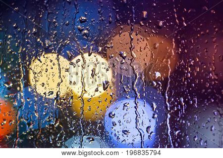 Rain dripping on the glass. Colorful background. Beautiful bokeh