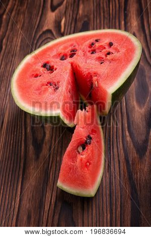 A view from above on a juicy red watermelon cut in half on a wooden table background. Tasteful and fresh sliced watermelon with little black seeds. A close-up of a colorful and ripe watermelon.