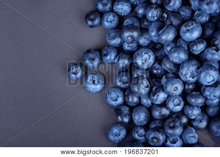A view from above on a heap of nutritious blueberries on a bright black background. Tasteful and ripe blueberries. Refreshing and healthful blueberries for sweet summer smoothies and yogurts.
