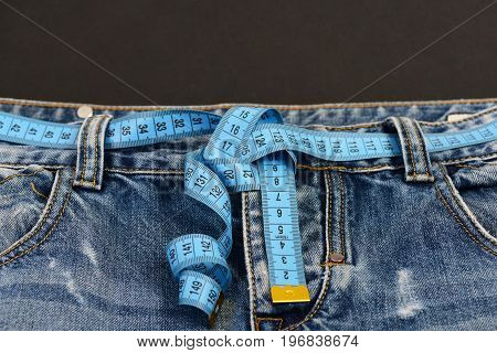 Healthy lifestyle and dieting concept. Close up of jeans with measure tape around waist. Top part of denim trousers isolated on black background. Blue jeans with blue measure tape instead of belt.