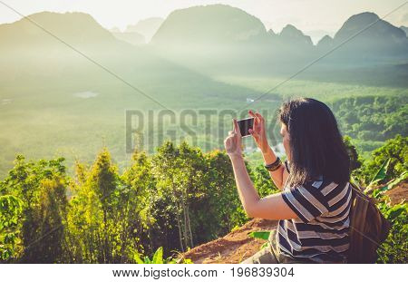Young traveler woman backpacker use mobile phone take a photo of beautiful of sunrise nature at top of mountain viewFreedom wanderlust conceptKhao Samed Nang CheePhang NgaThailand.