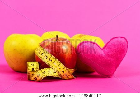 Concept of weight loss useful food and health: apples and yellow tape for measuring near heart isolated on pink background