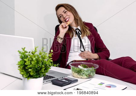 Smiling young woman with legs on table and eating a salad. Horizontal indoors shot.