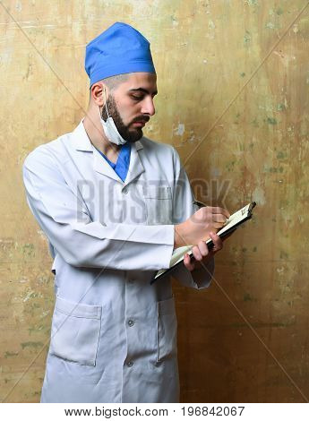 Doctor With Beard And Serious Face Writes Note
