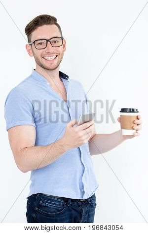 Excited young manager ready for work. Energetic handsome businessman drinking coffee and using smartphone. Optimistic intelligent man in eyeglasses looking at camera. Good day for business concept