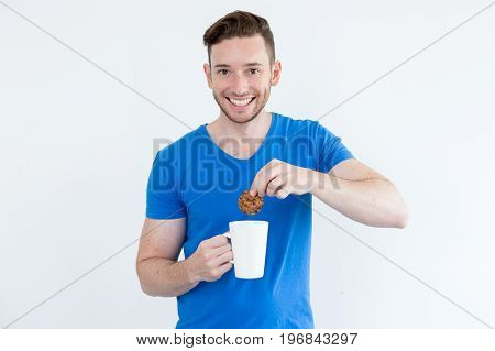 Happy handsome young man immersing cookie into warm beverage and looking at camera. Cheerful guy enjoying tea time. Coffee break concept