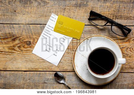 credit card for paying, cup of coffee and check on cafe wooden desk background top view