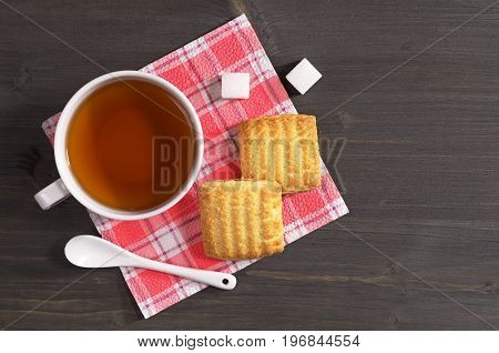 Cup of tea and shortbread cookies with jam on dark wooden table top view