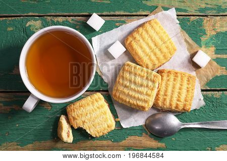 Cup of tea and shortbread cookies with jam on old green table top view