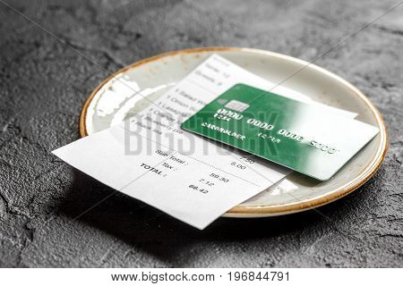 plate and receipt bill for payment by credit card on dark table background