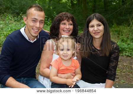 Young Family In Fun At Park With Grandparent Mother In Vacation