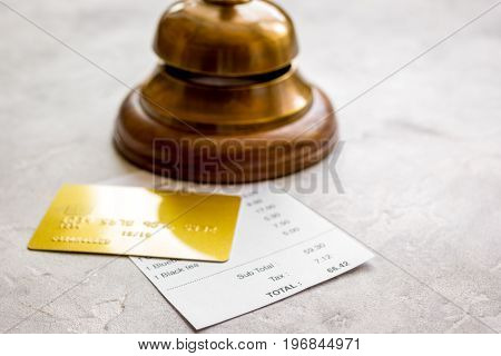 restaurant bill paying by credit card and waiter ring on stone table background