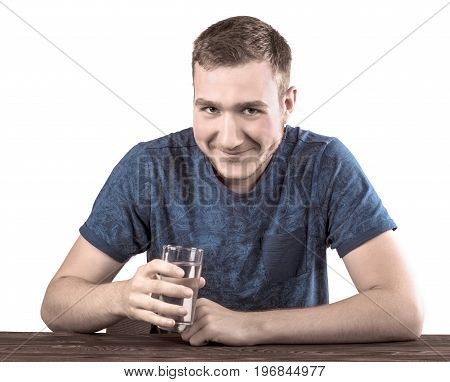 A young male with a glass of water in his hand, isolated on a white background. The man in a blue T-shirt with a malicious grin. The guy drinks water.