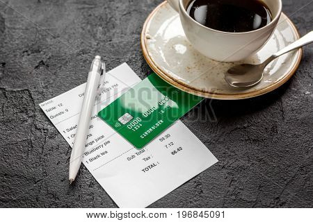 restaurant bill paying by credit card for cup of coffee on dark table background