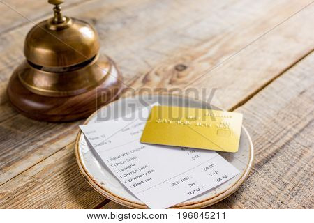 restaurant bill, credit card and waiter ring on wooden table background