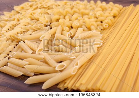 Close-up picture of different types and shapes of Italian pasta on a table. Assorted types of pasta: maccheroni, fusilli, penne and farfalle. Flour products.