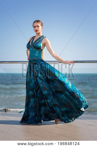 A wonderful, elegant and pretty lady in a long waving emerald dress, posing near a bright blue sea. The gorgeous woman on vacation on the sea or ocean.