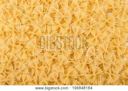 Uncooked bow-tie or farfalle pasta. Tasty traditional farfalle Italian macaroni. High quality, delicious, hard, raw and bright yellow texture close-up. Flour products.