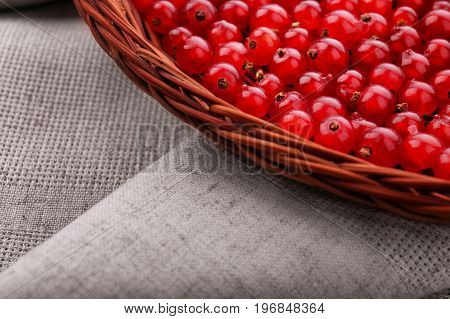 Fresh, juicy, tasty red currant in a wooden basket. Bright red berries on a gray background. Colorful red currant in the brown basket. Vegetarian food.