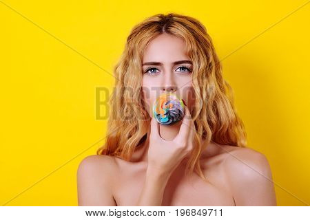 Young Blondy Female Model With Long Wavy Hair Holding Delicious Cupcake Over Yellow Background.