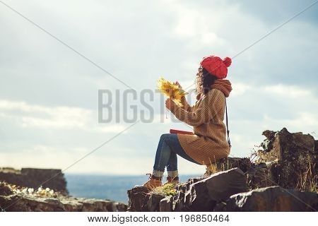 Young Woman On The Top Of A Rock Enjoys The View Of Sunset Over An Autumn Forest. Lifestyle And Autu