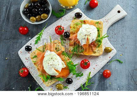 Poached egg on grilled toast with smoked salmon, rucola, olives, vegetables and orange juice. on white board. healthy breakfast.