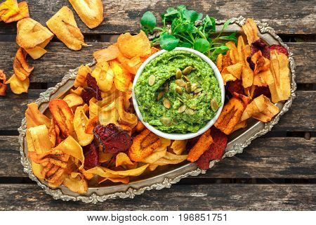 Home made vegetable crisps from carrots, parsnips and beetroot with watercress guacamole.
