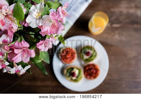Still life of flowers newspaper breakfast with cakes and glass of juice on kitchen table