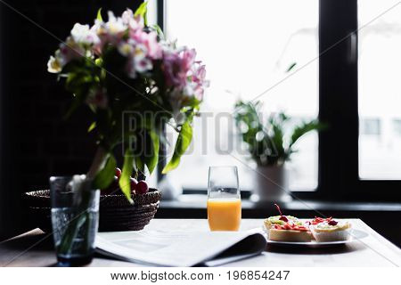 Still Life Of Newspaper, Breakfast With Cakes And Glass Of Juice On Kitchen Table In Front Of Window
