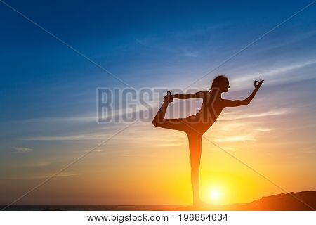 Silhouette of young woman doing fitness exercises on the sea beach during amazing sunset. Yoga and healthy life style.