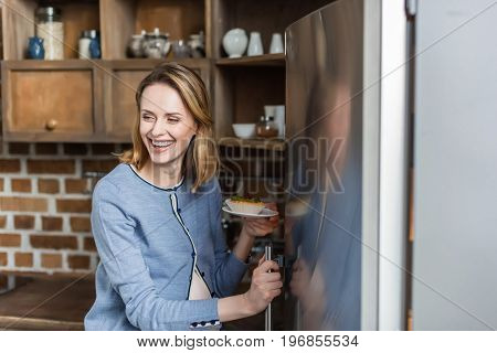 Portrait Of Young Pregnant Woman Taking Food From Fridge In Kitchen