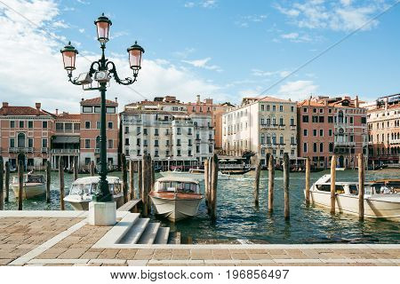 VENICE, ITALY - JULY 03, 2017: Private boats and taxis moored on Grand Canal in Venice on a bright summer day. Boats are the main mode of transport in the city.