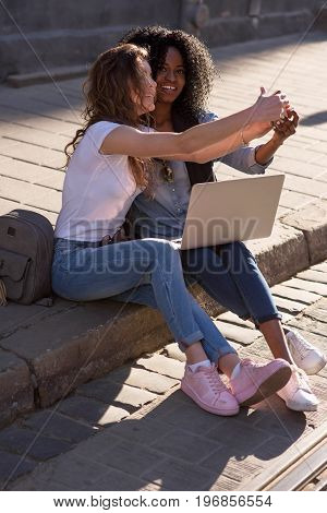 Two girls sitting on the pavement with the laptop and making selfie. One girl is black. Girls wearing casual clothes.