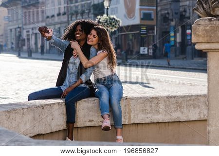 Selfie of two attractive girls near the monument in beautiful city. One black girl with her friend. Girls wearing casual clothes.